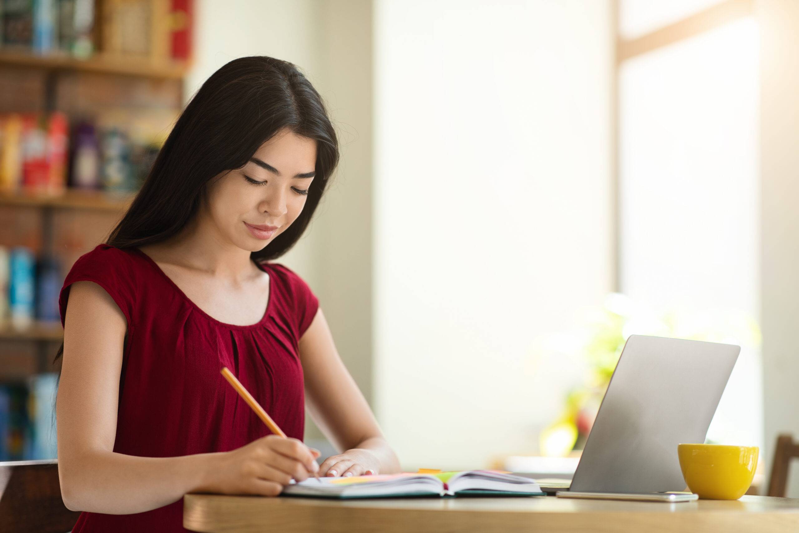 Beautiful Asian Student Girl Studying With Laptop In Cafe And Taking Notes